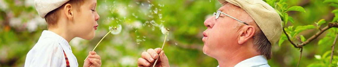 Mann und Kind mit Pusteblumen, für Allergien Hautarzt Dr. Kautz in Konz